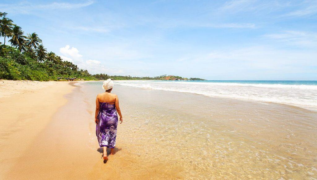 Frau zu Fuß am Strand nach Ayurveda-Behandlung in Sri Lanka