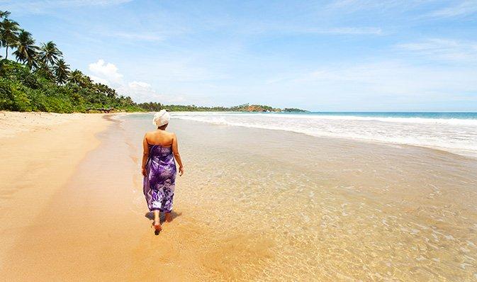 Una signora che cammina lungo la spiaggia durante il suo viaggio Ayurvedico